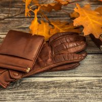 Closeup of luxurious leather items for winter season outfit on vintage wooden background