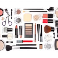 makeup cosmetics and brushes on white background top view