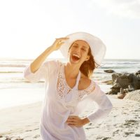Carefree woman walking on beach with sun dress and hat